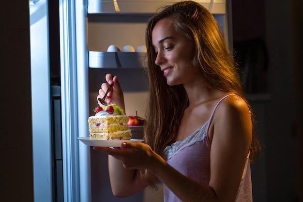 Голодная женщина в пижаме ест сладкий пирог ночью возле холодильника