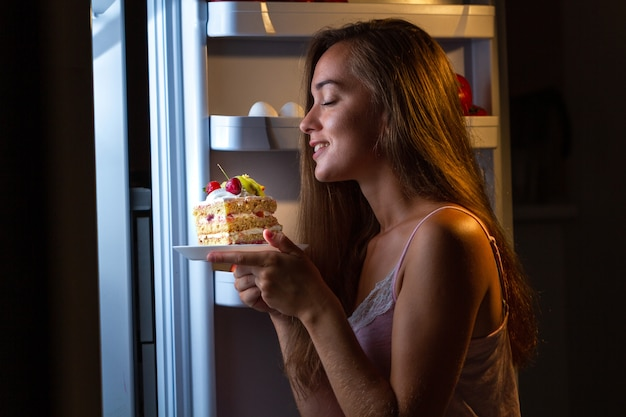 Hungry woman in pajamas eating sweet cake at night near fridge