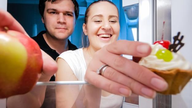 夜遅くの軽食のために冷蔵庫の食べ物を取っている空腹の若いカップル。