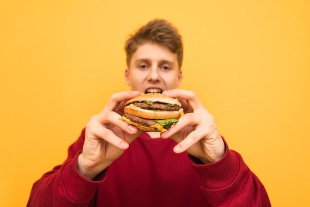 Голодный молодой человек держит в руках вкусный большой бургер