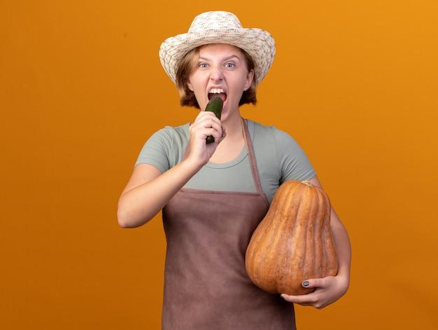 Голодная молодая славянская женщина-садовник в садовой шляпе держит тыкву и кусает огурец