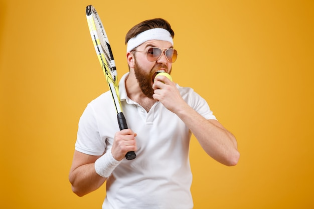 Голодный молодой теннисист кусает теннисный мяч.