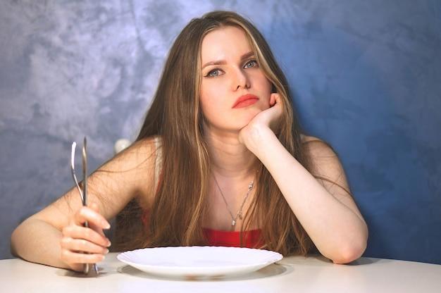空の皿で待っている空腹の若い女性
