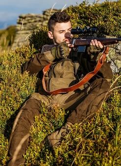 狩猟用ライフルを狩ります。ハンターマン。狩猟期間。銃を持った男性。閉じる。狩猟銃と狩猟フォームを持ったハンター。ハンターが狙っている。ターゲットでのシューターの目撃。男は狩りをしている。