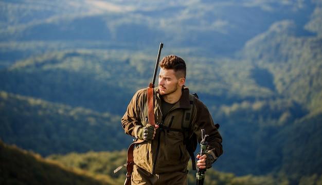 狩猟用ライフルを狩る。ハンター男。狩猟期間。銃を持つ男性。