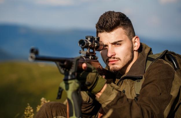 狩猟用ライフルを狩ります。ハンターマン。ターゲットでのシューターの目撃。狩猟期間。銃を持った男性。閉じる。狩猟銃と狩猟フォームを持ったハンター。ハンターが狙っている。男は狩りをしている。