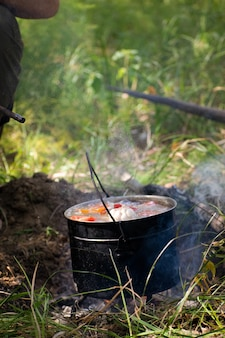 A hunter cooks shurpa in a bowler hat on the fire in nature