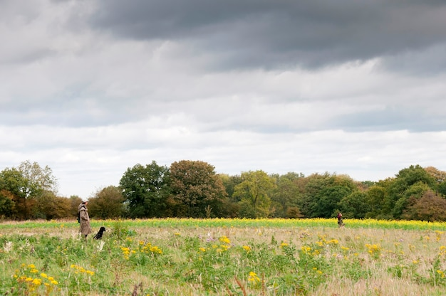 A hunter and his dogs in a field