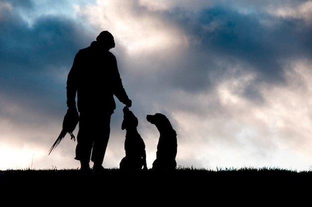 A hunter and his dogs silhouetted against the sky