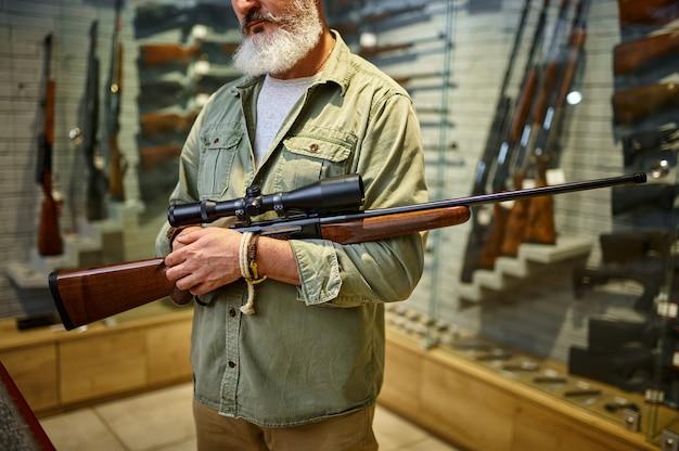 Охотник держит винтовку с оптическим прицелом в оружейном магазине