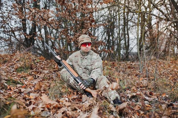 狩猟用ライフルを持った制服を着たハンター