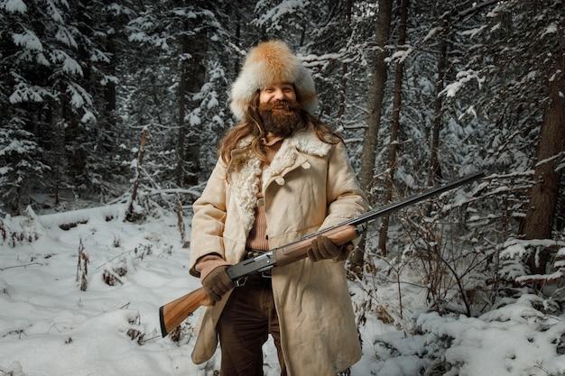 Охотник в винтажной одежде с оружием пробирается через лес