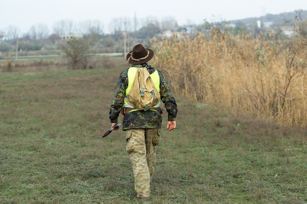Hunter man in camouflage with a gun during the hunt in search of wild birds or game