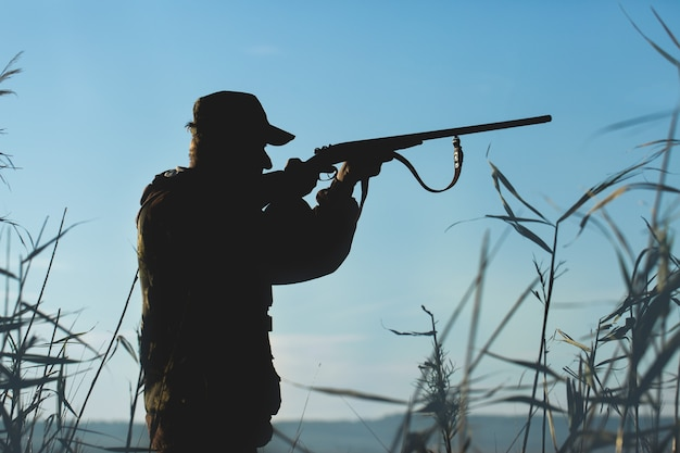 Hunter man in camouflage with a gun during the hunt in search of wild birds