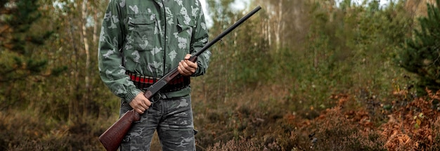 Hunter man in camouflage with a gun during the hunt
