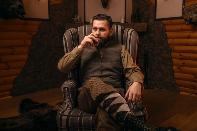 Человек-охотник пьет алкоголь после успешной охоты