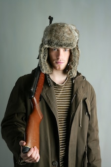 Hunter man fur winter hat holding rifle gun