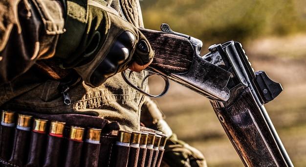 ハンターマン。狩猟期間、秋の季節。銃を持った男性。秋の森で狩りをする狩猟銃と狩猟形態を持ったハンター。男は狩りをしている。バックパックと狩猟銃を持ったハンター。