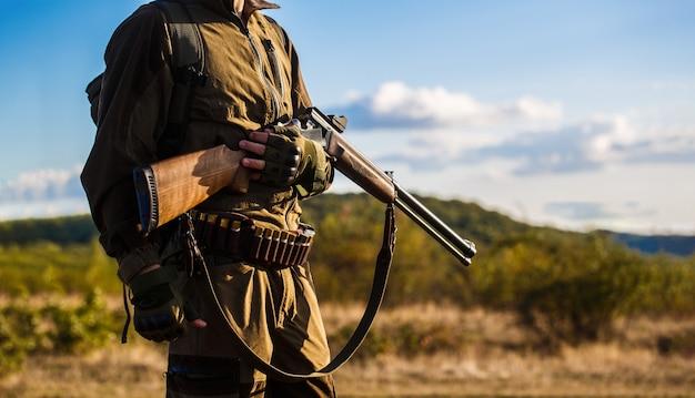 ハンター男。狩猟期間、秋のシーズン。銃を持った男性。バックパックと狩猟銃を持つハンター。