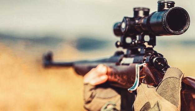 Человек-охотник. период охоты. мужчина с ружьем. закройте вверх. охотник с охотничьим ружьем и охотничьей формой для охоты. охотник целится. прицеливание стрелка в цель. мужчина на охоте. охотничье ружье.