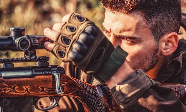 ハンターマン。狩猟期間。銃を持った男性。閉じる。狩猟銃と狩猟フォームを持ったハンター。ハンターが狙っている