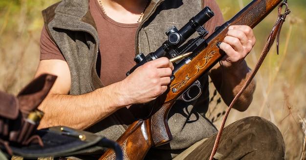 ハンターマン。狩猟期間。銃、ライフルを持つ男性。男は狩猟用ライフルを充電しています。閉じる。狩猟シーズン中の狩猟のプロセス。狩りの準備ができている男性ハンター。男は狩り、スポーツをしている。