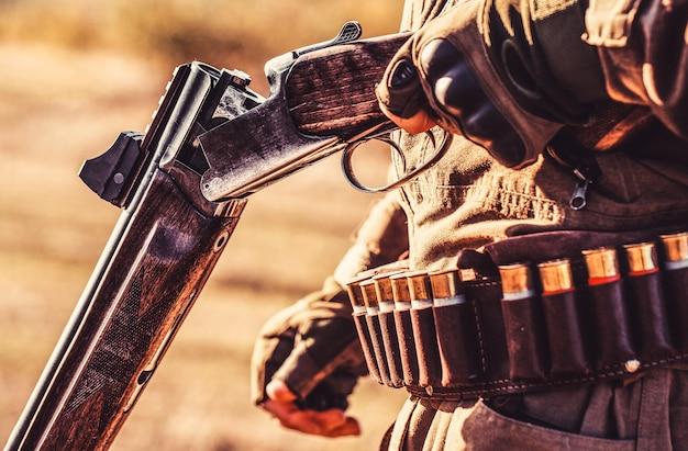 ハンターマン。狩猟期間。銃、ライフルを持つ男性。男は狩猟用ライフルを充電しています。狩りの準備ができている男性ハンター。閉じる。男は狩り、スポーツをしている。