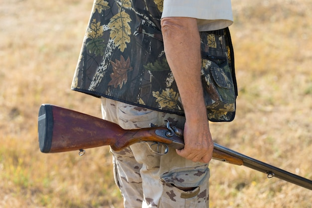 Человек-охотник в камуфляже с ружьем во время охоты в поисках диких птиц или дичи. осенний сезон охоты.