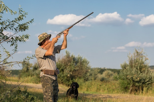野鳥やゲームを探して狩り中に銃を持ったカモフラージュのハンター男。秋の狩猟シーズン。