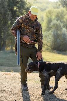 Человек-охотник в камуфляже с ружьем во время охоты в поисках диких птиц или дичи