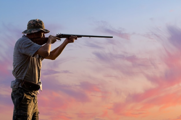野鳥やゲームを探して狩り中に銃でカモフラージュのハンター男