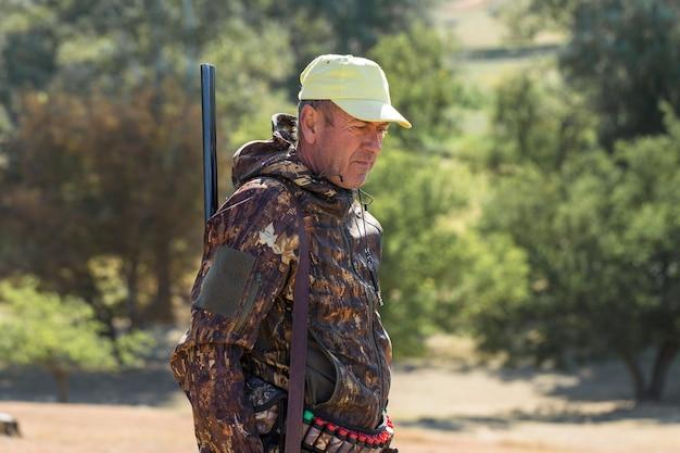 野鳥を探す狩猟中に銃を持った迷彩のハンター男