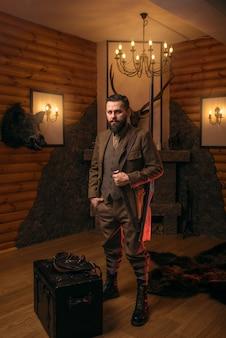 Охотник со старым ружьем в старинной традиционной охотничьей одежде, стоящей против античного сундука.