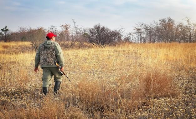 Охотник движется с ружьем в поисках добычи. охотник с ружьем. охота на зайца