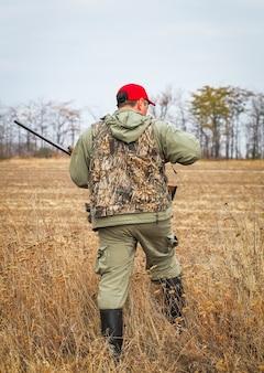Охотник движется с ружьем в поисках добычи.