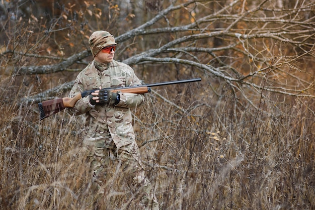 Hunter in uniform with a hunting rifle
