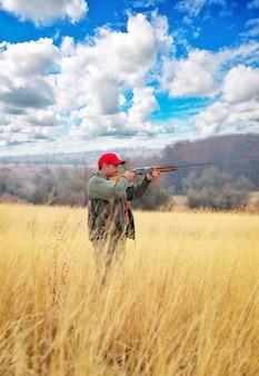 Охотник с ружьем. охотник целится в цель. охота на зайца