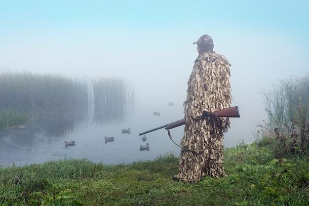 산탄총을 든 사냥꾼이 호수에서 오리를 추적합니다. 오리 사냥.