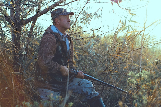 A hunter with a gun in his hands in hunting clothes in the autumn forest in search of a trophy