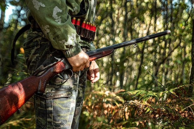 Hunter with a gun in his hands in hunting clothes in the autumn forest