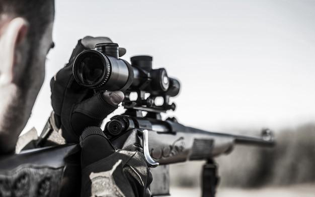 Охотник с охотничьим ружьем и охотничьей формой для охоты. охотник целится. стрелок