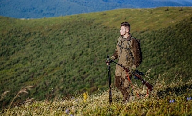 Охотник с охотничьим ружьем и охотничьей формой для охоты. охотник целится. мужчина на охоте. охотничье ружье. человек-охотник. период охоты. мужчина с ружьем.
