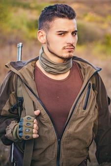 Охотник с ружьем на охоте. портрет здоровенного охотника