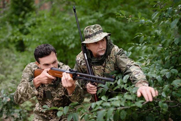 Hunters ambushing aiming father instructing son.