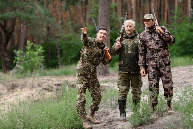 Hunters father and sons guy pointing to wildfowl