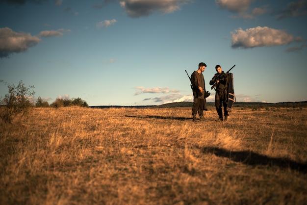 狩りに散弾銃を持ったhunters。狩猟用ライフルの口径。迷彩服を着たhunters