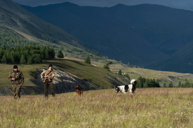 Hunters with their dogs walk in the steppe surrounded by mountains