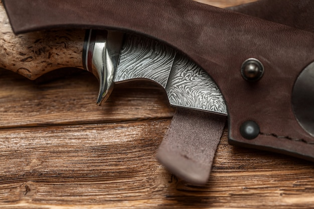 Hunting damascus steel knife handmade on a wooden surface, close-up