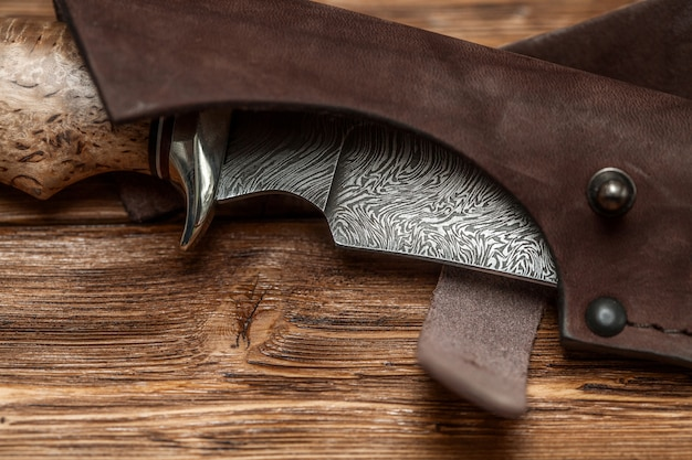 Hunting damascus steel knife handmade on a wooden surface