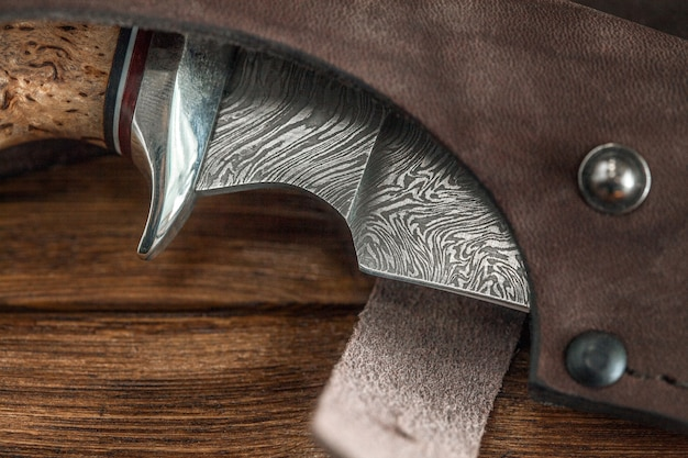 Hunting damascus steel knife handmade on a wooden wall, close-up